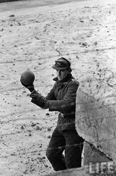 Пограничник Пограничник из Восточной Германии перебрасывает мяч через Берлинскую стену, 1962 год