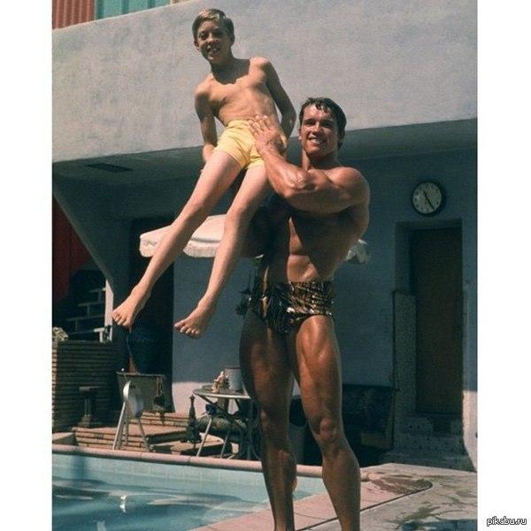 Редкое фото Арнольд Шварценеггер надевает мальчика на руку